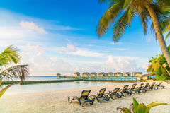 Beach chairs in Maldives island with water villas at the sunrise Stock Image