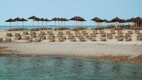 Beach with beach chairs in morning light on the beach. Of a Mediterranean seaside holiday resort, no people, early morning stock footage