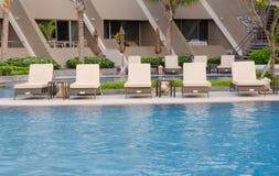 Beach chairs near swimming pool Stock Photo