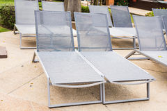 Beach chairs near swimming pool Stock Photos