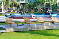 Beach chairs near swimming pool in garden Stock Images
