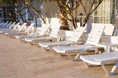 Beach chairs near swimming pool Stock Photos