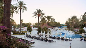 Beach chairs near swimming pool in luxury hotel resort. Turkey, Kemer. Beach chairs and palms near swimming pool in luxury hotel resort. Turkey, Kemer stock video footage