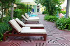 Beach chairs near swimming pool in tropical resort Royalty Free Stock Images