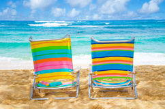 Beach chairs by the ocean. Two colorful beach chairs under by the ocean with sunscreen, with couple in the ocean on background Royalty Free Stock Images