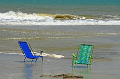 Beach Chairs Ocean Water Sand Peaceful. Two beach chairs sitting in beach sand in the edge of the ocean waters with waves crashing in the background Stock Images