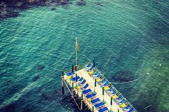 Beach chairs and parasols on a wooden pier in Sorrento coast. Campania, Italy royalty free stock images