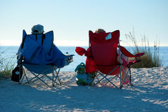 Beach chairs with people. Low set sun on people in beach chairs at the beach on a sunny afternoon Stock Image