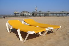 Beach Chairs and the Pier. Two yellow beach chairs with the Scheveningen pier in the background stock photography