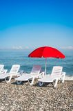 Beach chairs and red umbrella on shingle beach Royalty Free Stock Image