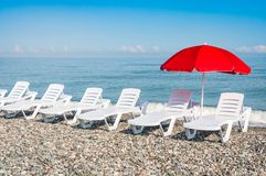 Beach chairs and red umbrella on shingle beach Stock Images