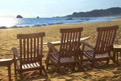 Beach chairs on sand beach in front of waves Stock Photography