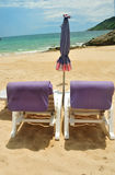 Beach chairs on sand in front of beach Royalty Free Stock Photos