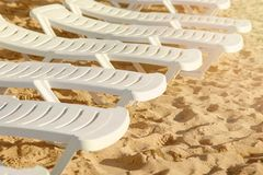 Beach chairs on the sand. Several free white beach chairs on the beach Stock Photos