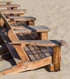 Beach Chairs in the Sand. Wooden beach chairs in the sand on a sunny day Royalty Free Stock Photo