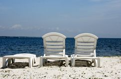 Beach Chairs on a sandy Ocean coastline. Beach chairs in the sun on an Ocean coastline royalty free stock photos