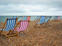 Beach Chairs on the shore at Brighton England. Brightly colored beach chairs on the shore at Brighton Beach in England Stock Image