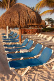 Beach Chairs in the Sun. A row of empty beach chairs in the morning sun on the sands of Playa Del Carmen, Mexico royalty free stock photography
