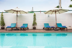 Beach chairs and swimming pool in the resort holiday. Stock Photos