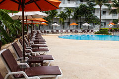 Beach chairs and swimming pool Stock Images