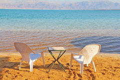 Beach chairs and a table waiting for tourists Royalty Free Stock Photo