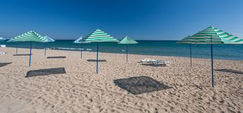 Beach with chairs and thatched umbrellas Stock Photo