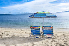 Beach chairs on tropical beach. Two blue beach chairs with umbrella on the water's edge of a tropical beach Royalty Free Stock Photo