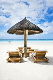 Beach chairs on tropical white sand beach. Beach chairs and umbrella on tropical white sand beach Stock Images