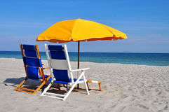 Beach Chairs. Two blue beach chairs with a yellow umbrella sitting on the sand by the ocean Stock Photography