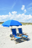 Beach chairs. Two pretty blue beach chairs and umbrella waiting for guest to enjoy the seashore Royalty Free Stock Photography