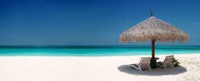Beach Chairs and Umbrella. On a beautiful island, panoramic view with much copy space Stock Image