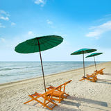 Beach chairs and umbrella on beach. Stock Photos