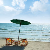 Beach chairs and umbrella on beach. Stock Images
