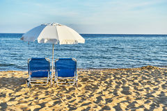 Beach chairs with umbrella and beautiful beach on a sunny day Stock Photography