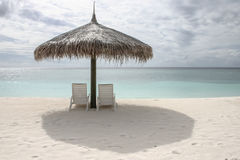 Beach chairs with umbrella in a cloudy sunny day Royalty Free Stock Image
