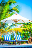 Beach chairs and umbrella at exotic tropical resort Stock Photo