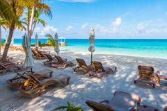 Beach chairs with umbrella at Maldives island with white sandy b Stock Photo