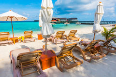 Beach chairs with umbrella at Maldives island with white sandy b Stock Photos