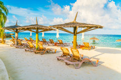 Beach chairs with umbrella at Maldives island, white sandy beach Royalty Free Stock Images