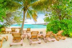 Beach chairs with umbrella at Maldives island, white sandy beach Stock Image
