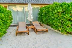 Beach chairs with umbrella at Maldives island, white sandy beach. And sea stock image