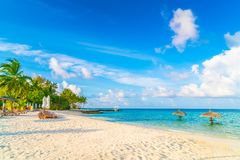 Beach chairs with umbrella at Maldives island, white sandy beach. And sea royalty free stock image