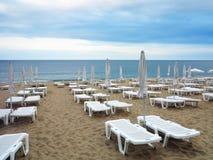 Beach chairs and umbrella on the sand near sea, blue sky Royalty Free Stock Photos