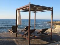 Beach chairs and umbrella on the sand near sea, blue sky Stock Photography