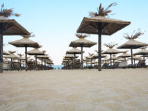 Beach chairs and umbrella on the sand near sea, blue sky Royalty Free Stock Photography