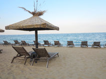 Beach chairs and umbrella on the sand near sea, blue sky Stock Images