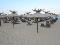Beach chairs and umbrella on the sand near sea, blue sky Stock Photo