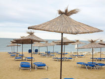 Beach chairs and umbrella on the sand near sea, blue sky Stock Photography