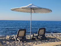Beach chairs and umbrella on the sand near sea, blue sky Stock Photos