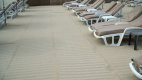 Beach chairs with umbrella on sand. A tilting down shot of beach chairs lining up with umbrellas on the sand near the beach stock video footage